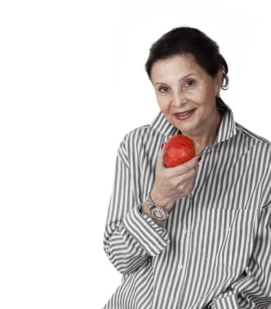 Close-up of mature woman smiling with an red apple against white background photo