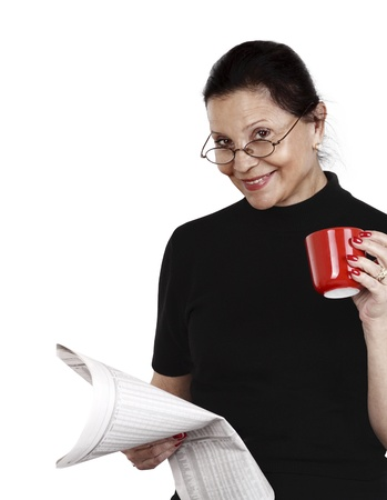 woman looks at newspaper and drinks her coffee against white background photo