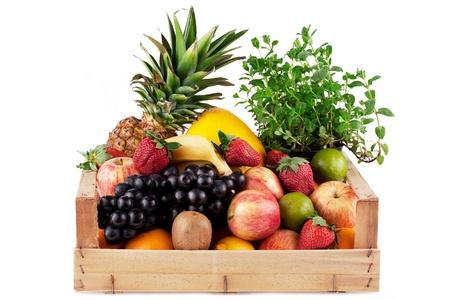 Früchte und Kräuter in Holzkiste, isoliert auf weiss
