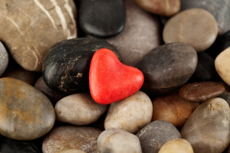 Red heart on pebbles