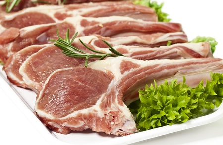 lamb chop ready for cooking, with fresh rosemary. Isolated on white. photo