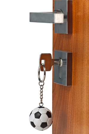 Door open with keys in lock and soccer ball key chain, isolated  Stock Photo - 9830591