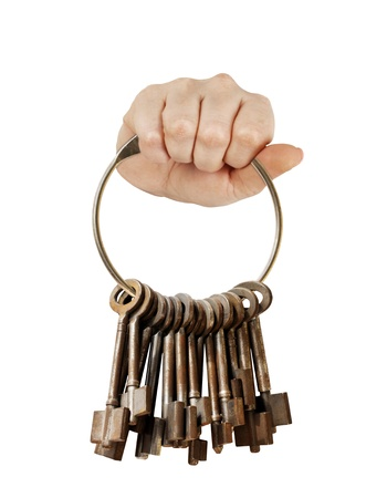 Fist with bunch of old keys on a big keyring. isolated on white Stock Photo - 9830579