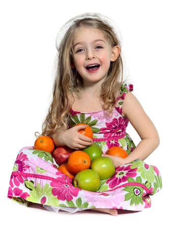 laughing small girl sitting down and holding Apples and Orange Stock Photo - 9830600