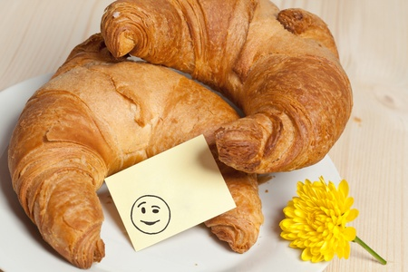 breakfast smiley face: Two Croissants with Smiley Sticky Note and Flower Stock Photo