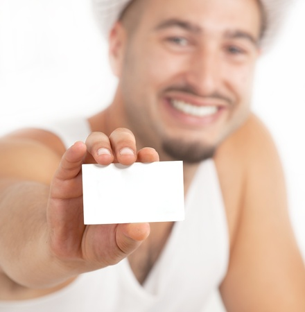 Portrait of a handsome young guy showing his business card  and smiling at viewer  photo