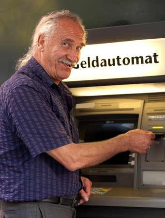 withdrawing: Senior Men withdrawing money from credit card at ATM and smiling Stock Photo