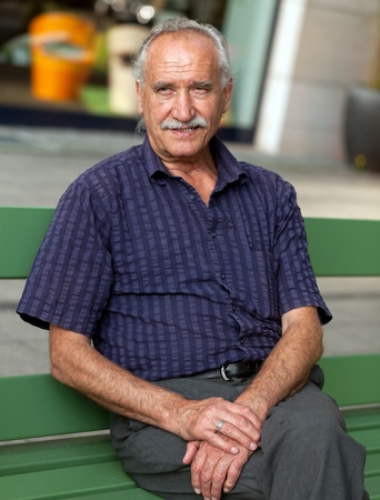 one senior man only: Cheerful senior man sitting outdoor on bench in the City