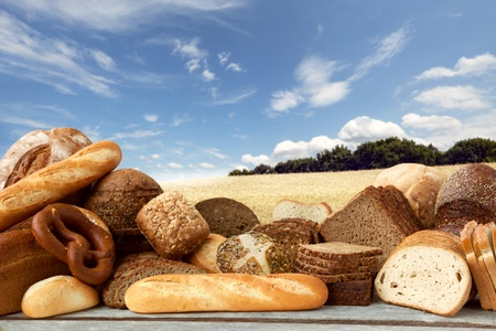 bakery products: Assortment of baked goods on Field of wheat under the blue sky background