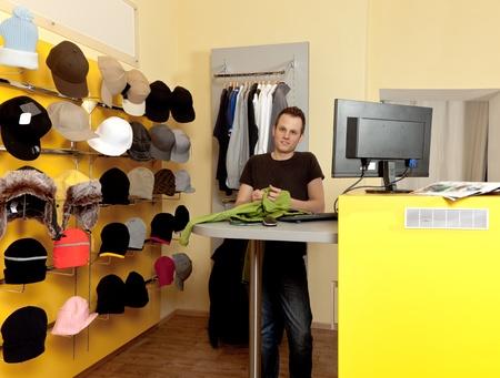kledingwinkel: Jonge man in haar kledingwinkel en glimlachen Stockfoto