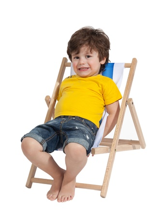 Adorable Toddler boy sitting on deck chair, isolated on white Imagens