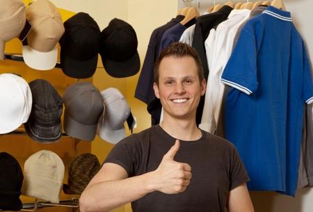 Junger Mann in ihrem Bekleidungsgeschäft lächelnd und zeigt Daumen nach oben Standard-Bild
