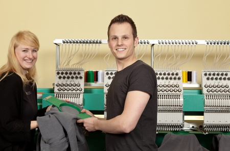 Portrait of a shop assistant and a Young Man in her Textile embroidery Shop Stock Photo