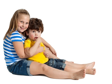 Adorable little boy and her Preschooler Sister sitting down, isolated on white Stock Photo - 12611511