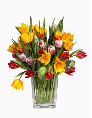 Tulipanes de primavera ramo en un florero de cristal, aislados en blanco