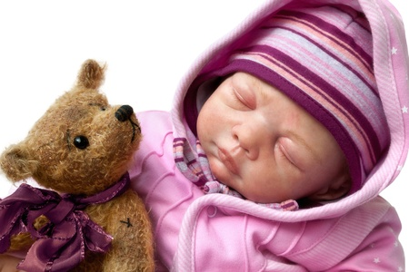 newborn baby doll sleeping with toy Teddy Bear isolated on white Background photo