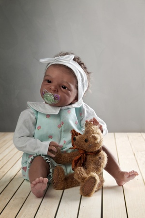 Cute African American Baby Doll sitting on a Wooden Floor with Teddy Bear photo