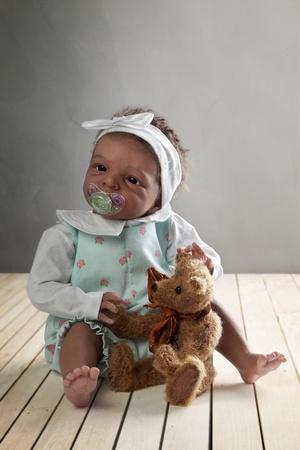 Cute African American Baby Doll sitting on a Wooden Floor with Teddy Bear Standard-Bild