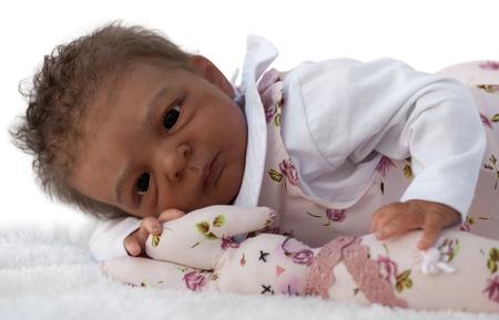 Ein neugeborenes Baby Doll Lying Down mit Bunny Toy, isoliert auf weiß