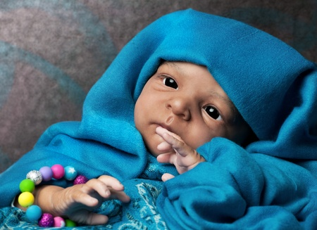 African American Baby Doll Portrait lying under turquoise blanket photo