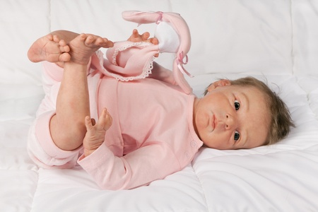 baby doll: Adorable baby playing with his feet, on white background
