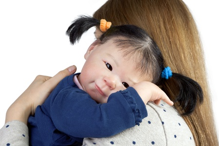 asian baby girl: Rear view of mother with cute asian baby girl looking over shoulder