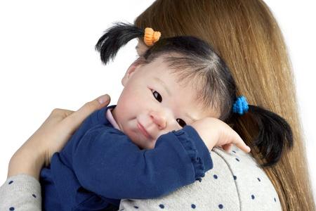 Vista trasera de la madre con la ni�a linda del beb� asi�tico mirando sobre el hombro Foto de archivo