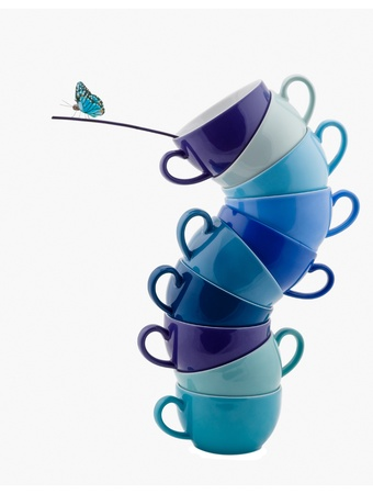 Stack of blue Coffee Cups whit Butterfly for Balance isolated on white photo