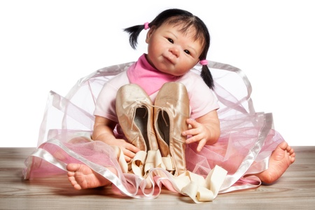 ballet slippers: Little cute ballerina Doll is sitting on the floor with Ballet slippers isolated on white Background