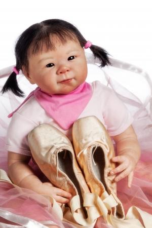 zapatillas ballet: Peque�a bailarina linda mu�eca est� sentado en el suelo con zapatillas de ballet aisladas sobre fondo blanco
