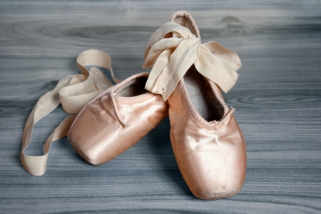 zapatillas de ballet sobre un piso de madera Bascjground Foto de archivo