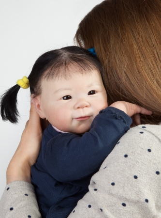 Rear view of mother with cute asian baby girl looking over shoulder  photo