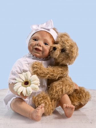 Teddy Bear embracing Baby Doll and sitting of the Floor with Flower photo