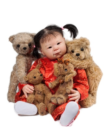 asian Baby Doll and Teddy Bears sitting on the Floor, isolated on white Background photo