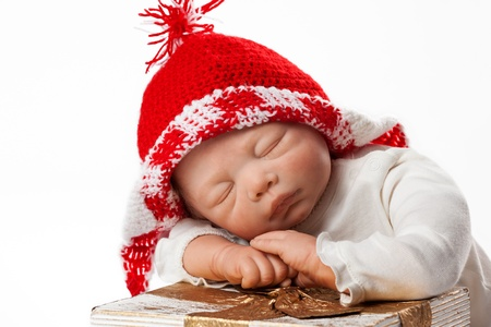 knit cap: Christmas Baby Doll Boy with Knit Cap sleeping on Gift Box