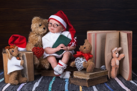 Christmas Baby Doll reading Book for Teddys and Toys Stock Photo