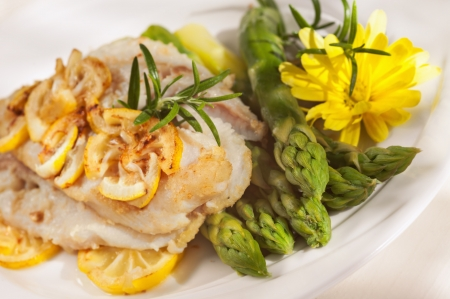 whitefish: pan seared fillet of white fish, lemon sauce and vegetables on white background