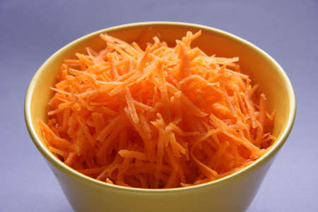Grated carrots in a yellow plate. 版權商用圖片