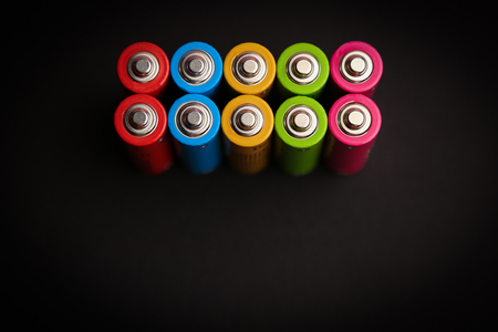 Energy abstract background set of colored alkaline AA size batteries on black background. the view from the top. place for text. minimalism.