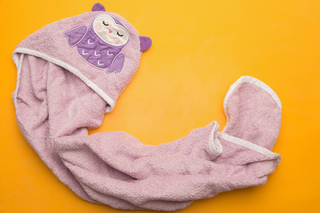 purple violet bathing baby towel on a yellow background. View from the top. Place for text. Flat lay Stock Photo