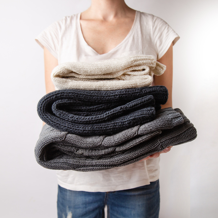 girl is holding a pile of washed and ironed clothes knitted sweaters in her hands on a white background.