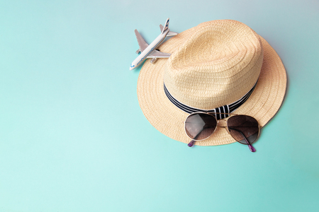 straw beach hat, sunglass and white airplane on blue background In the summer, copy space,Top view,minimal style.