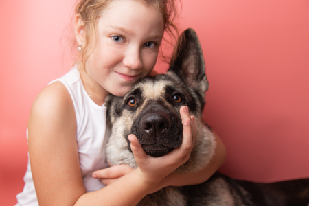 portrait of a cute young caucasian girl in white t-shirt with a German Shepherd, keeps face on pink backgraund.