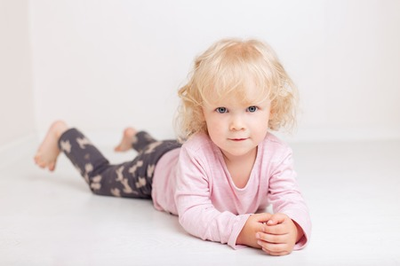 curly blonde baby girl in comfortable home casual clothes is lying on the floor in a bright white room smiling and looking at the camera Фото со стока