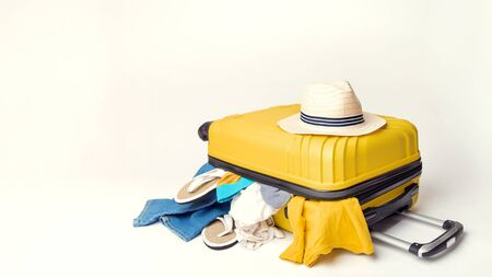 hat on a yellow suitcase with things of the traveler on a white background. banner. Travel and adventure concept
