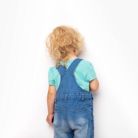 Fille bouclée caucasienne punie et debout contre un mur. Banque d'images