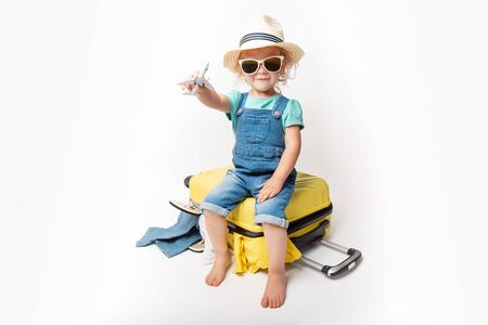 Funny curly little baby girl in a hat, T-shirt and jeans with a yellow suitcase is smiling on white background waiting for an airplane. concept trip with kids. Stock fotó