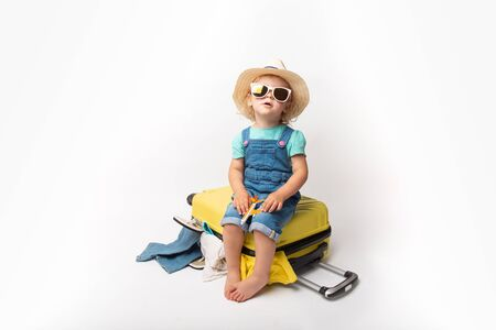 Funny curly little baby girl in a hat, T-shirt and jeans with a yellow suitcase is smiling on white background waiting for an airplane. concept trip with kids.
