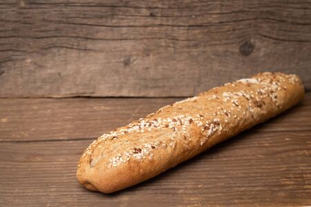 french baguette with sesame seeds on old wooden background. fresh bakery