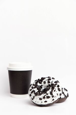 paper cup with coffee and Delicious fresh donuts black and white color with white icing and chocolate chips closeup on a white background. vertical